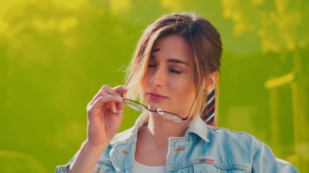 Zavři tu krásnou kavkazskou mladou dívku, jak si bere brýle a usměje se do kamery na žlutém pozadí. Mimo. Portrét.