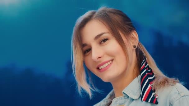 Veselá, kavkazská mladá dívka, která hledí do kamery a vesele se směje na modrém skle. Zavři to. Portrét.
