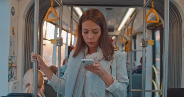 Portrait of cute brunette girl holds the handrail, texting and browsing on mobile phone in public transport. Woman using the smartphone. City, urban background.
