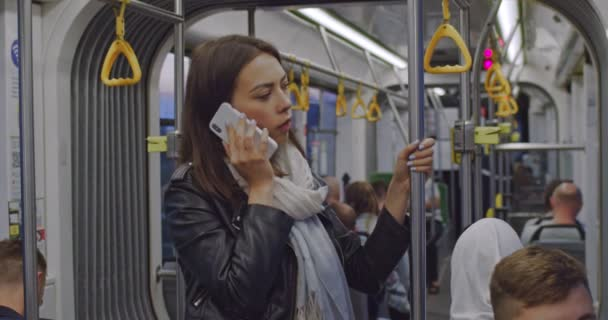 Sad girl holds the handrail, and speaks on the cell phone in public transport in evening city. Depressed woman standing and talking on smartphone in city tram during her daily commute.