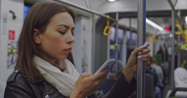 Kaukázusi fiatal, gyönyörű nő áll a villamoson, és fogja a korlátot, miközben beír egy üzenetet a mobiltelefonba. Közelről..