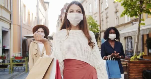 Açık havadan alışveriş yapan çok ırklı kadınlar. Tıbbi maskeli güzel beyaz bir kızın portresi şehirde duruyor. Maskeli güzel bir Afro-Amerikalı kadın. Karantina konsepti