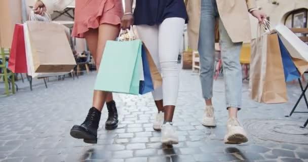 Portrét smíšených závodnic venku s nákupy. Zblízka ženské nohy kráčející po městě. Různé ženy v kalhotách a sukni chodí po ulici. Po nakupování. nákupní tašky. Urban concept