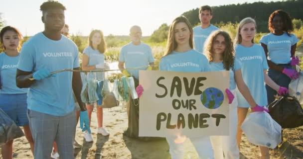 Gruppe multiethnischer Freiwilliger, die gegen Umweltverschmutzung protestieren. Enthusiastische Öko-Aktivisten mit einem Plakat Save Our Planet und Müllsäcken, die in die Kamera schauen. Ökologie, naturschutzfachliches Konzept.