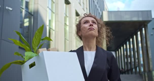 Young woman worker in a formal suit walking around the business district, viewing the scyscapers. Beautiful curly haired accountant holding a box with a job stuff outdoors. Hiring, traineeship.