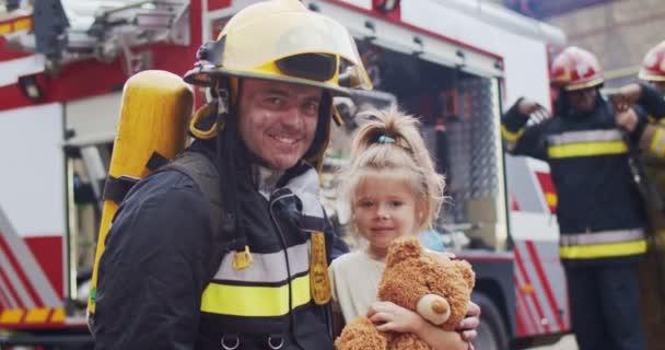Tűzoltó ölelés megmentett kislány játékmackóval. A rémült gyermek örül a megmentésnek. A tűzoltók hátterében, miután tüzet oltottak a tűzoltókocsi mellett. Életmentés, tűzbiztonság