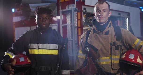 Střední plán dvou hasičů Afroameričanů a Kavkazanů v racku, kteří v noci stáli vedle auta a drželi se za přilby. Koncept záchrany životů, hrdinské profese, požární bezpečnosti