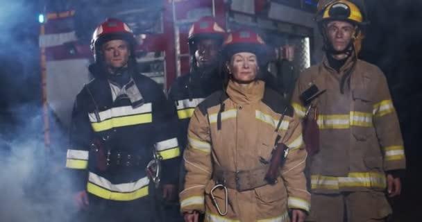 Střední plán čtyř hasičů přijíždějících z hasičské dodávky v plné výbavě s nouzovým záchranným nářadím a dívajících se v noci do kamery s úsměvem. Koncept záchrany životů, požární bezpečnost
