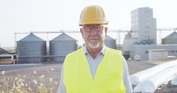 Porträt eines leitenden Wirtschaftsingenieurs mit Brille, Schutzmütze und Schwimmweste, der neben einer großen Industriefabrik steht und in die Kamera blickt. Studienkonzept Industrie und Technik .