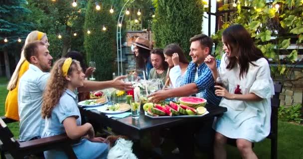 Junge multiethnische Menschen essen und trinken gemeinsam auf einer Gartenparty. Afroamerikanische und kaukasische Mädchen lachen. Fröhliche Jungs und asiatische Frauen plaudern. Freunde gehen an Gericht vorbei. Spaßkonzept