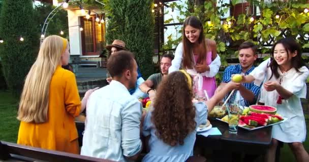 Fröhliche junge Leute essen und trinken auf Partys im Garten. Afroamerikanische und kaukasische Mädchen klirren mit ihren Brillen. Schöne Männer, die an Geschirr vorbeigehen. Asiatin lächelt. Sommerzeit. Festkonzept