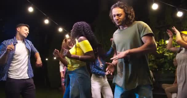 Happy African American girl and Caucasian boy having fun and dancing outdoor. Joyful mixed-races young friends moving to music at party in garden. Beautiful female in hat dances. Party concept