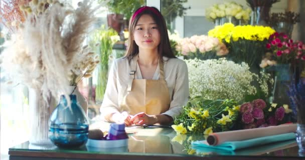 Beatiful young Asian woman in apron standing at table with equipment, colored papers for bouqet decorating. Attractive female florist looking at camera and smiling. Flower, houseplant shop, business.