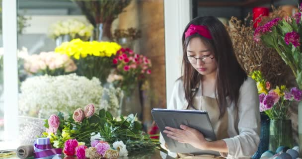 Concentrated young female florist working in flower shop. Attractive Asian woman in glasses using digital tablet in store taking inventory of flowers. Business, modern technology and nature concept.