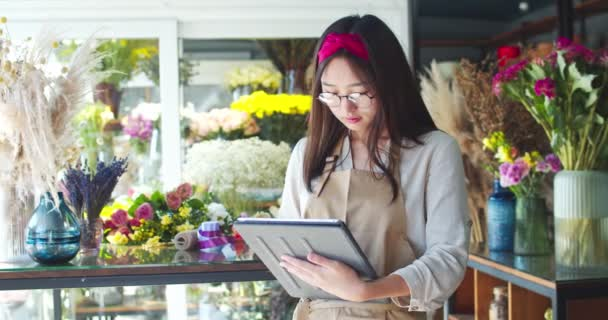Attractive Asian woman working in apron working in flower store. Young female florist using digital tablet to check availability and take inventory. Pretty shop owner in glasses smiling at camera.