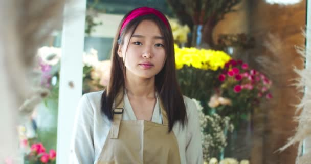 Portrait of charming Asian female show owner wearing apron in flower store. Attractive young woman florist looking to camera and smiling. People, professions, business, nature concept.