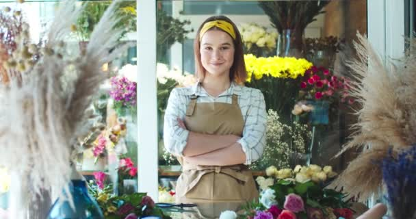 Charming young woman shop owner wearing apron, working in flower store. Attractive Caucasian female florist crossing arms and looking at camera. Business, entreprenuership, nature concept.