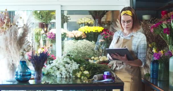Good-looking Caucasian woman wearing apron, working in flower store. Pretty young female florist in glasses taking inventory, using tablet and overlooking blossoms. Business, technology concept.