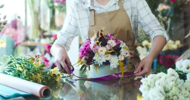 Nahaufnahme von charmanten jungen kaukasischen Floristen, die Schürze tragen und Strauß herstellen. Schöne Blumenverkäuferin schmückt, bindet lila Band um Hutschachtel mit Blüten. Business, Natur-Konzept.