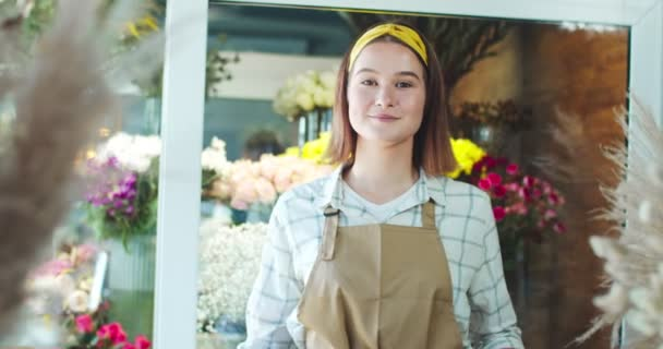 Happy Caucasian female flower shop seller wearing apron in modern store. Good-looking young woman florist crossing arms, looking at camera and smiling. Business, entreprenuership, nature concept.