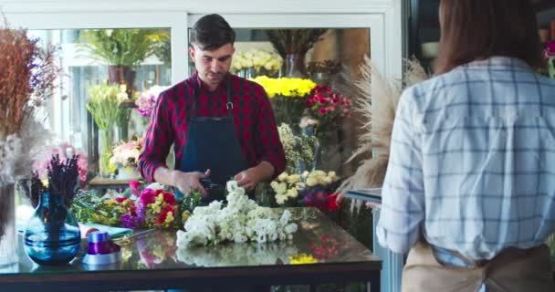 Charming Caucasian man florist taking flowers and cutting stems in store. Pretty young woman worker calling customer, client and typing on tablet. Business, technology, profession concept.