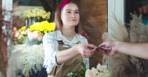 Charming female seller receiving money from customer and giving him order in flower store. Young Caucasian man client giving payment and taking bouquet of roses from florist. Commerce, business.