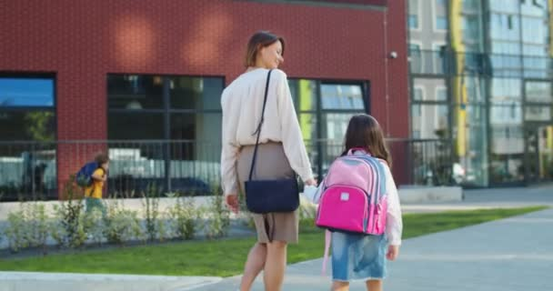 Back view of beautiful Caucasian woman walking with little daughter pupil to school and speaking on sunny day. Happy mother leads girl with pink backpack to lessons and talking. Knowledge concept