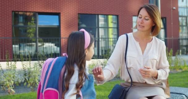 Egy gyönyörű kaukázusi nő portréja, aki a padon ül az iskola előtt, egy aranyos iskoláslánnyal a szabadban. Boldog anya beszél a lányával, és odaadja neki a csomagot reggelivel óra előtt..
