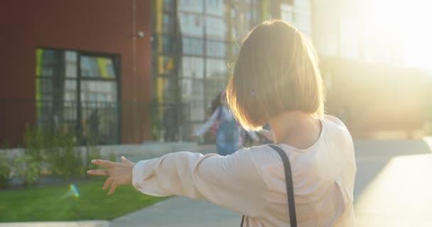 Kaukázusi gyönyörű anya találkozik aranyos kislánnyal az iskolából óra után a napfényben. Egy boldog iskolás lány portréja rózsaszín hátizsákkal az anyjához rohan és megöleli. Közelkép