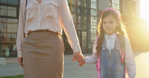 Kaukázusi nő fogja a kisiskolás lány kezét, és az utcán sétál iskolába. A kisiskolás lány portréja órákra jár anyával napfényben. Vissza a suliba. Tanulmányi koncepció