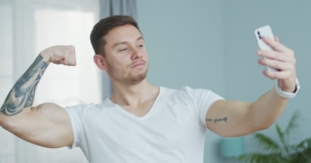 Bělošský svalnatý sportovec, který má video chat na smartphonu, ukazuje svaly, biceps doma. Volá pohledný mladík, mluví na kameře, usmívá se a směje. Samoizolační koncept.