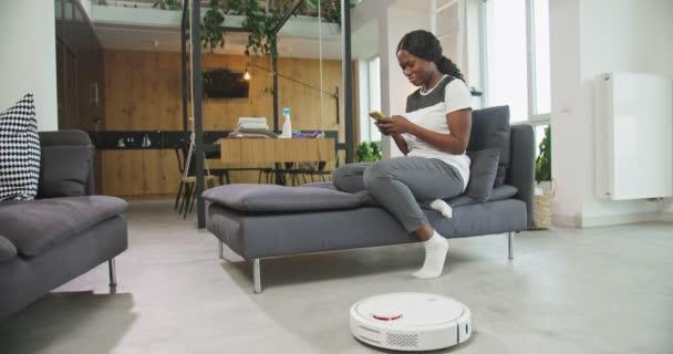 Die lächelnde junge afrikanisch-amerikanische Hausbesitzerin sitzt mit ihrem Smartphone auf dem Sofa im Wohnzimmer, während ein Staubsaugerroboter den Boden putzt und Hausarbeit erledigt. Erfindungen und Alltagskonzept.