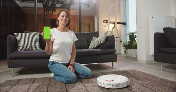 Střední plán šťastné ženy sedící na podlaze za robotickým vysavačem, držící telefon s chromakey. Roztomilá žena ukazující telefon se zelenou obrazovkou. Moderní technologie, vedení domácnosti, životní styl.