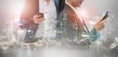 Mladí podnikatelé pomocí mobilního telefonu s pozadím budovy moderní město. Budoucí telekomunikační technika a internet věcí (Iot) koncepce.