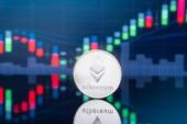 Ethereum (Eth), és cryptocurrency a befektetési koncepció - fizikai fém ethereum érmék, a globális kereskedelmi exchange piaci ár chart-a háttérben.