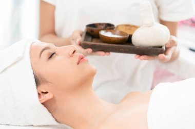 Relaxed woman lying on spa bed prepared for spa massage with therapist holding spa treatment set in background. Luxury wellness, stress relief and rejuvenation concept.