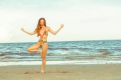 Young woman practicing yoga pose on the beach in summer. Healthy lifestyle and meditation.