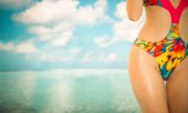 Fotografie Happy young woman wearing swimsuit at tropical sand beach resort in summer for holiday travel vacation.