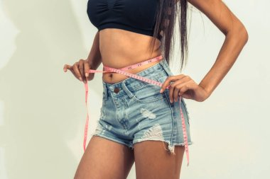 Young slim woman measures her waist by measuring tape after diet against white backgrounds. Concept of weight loss success.