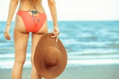 Boldog fiatal nő visel fürdőruhát birtoklás időben trópusi tengerparton nyáron vonatkozó nyaralás utazás.
