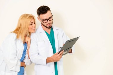 GP doctor looks at data in documents on clipboard while discussing with surgical doctor on white background. Medical service and healthcare concept.