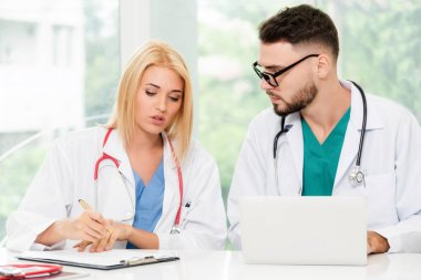 Young female doctor works at office in hospital while talking to male doctor sitting beside her. Medical service and healthcare concept.