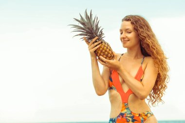 Happy young woman wearing swimsuit on tropical sand beach in summer for holiday travel vacation.