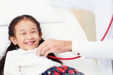 Young male doctor examining little kid in hospital office. The kid is happy and not afraid of the doctor. Medical children healthcare concept.