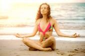 Mladá žena cvičí jóga pozice na pláži v létě. Zdravého životního stylu a meditace.