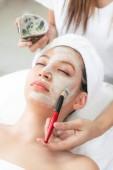 Schöne Frau mit einer kosmetischen Peelingbehandlung für das Gesicht von einem professionellen Dermatologen im Wellness-Spa. Anti-Aging, Gesichtspflege und luxuriöses Lifestylekonzept.