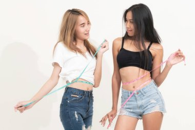 Two young slim woman measure their waist by measuring tape after diet against white backgrounds. Concept of weight loss success and slimming competitions.
