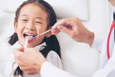 Friendly young dentist examining happy child teeth in dental clinic. Dentistry concept.