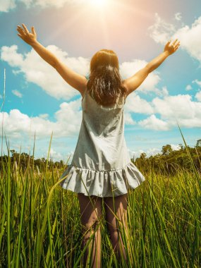 Young beautiful woman on green grass meadow spreading arms to the blue sunny sky on summer day. Getaway and meditation concept.