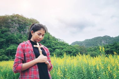 Young beautiful woman praying on nature background. Hope and faith concept.